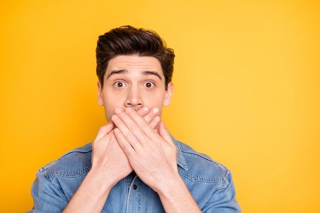 Zamknij zdjęcie zdziwionego mężczyzny zakrywającego usta po powiedzeniu informacji, których nie powinien mieć z otwartymi oczami szeroko izolowana żywa kolorowa ściana