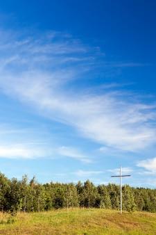 Zamontowany na wzgórzu metalowy krzyż w pobliżu lasu mieszanego, symbole religijne w przyrodzie, letni krajobraz