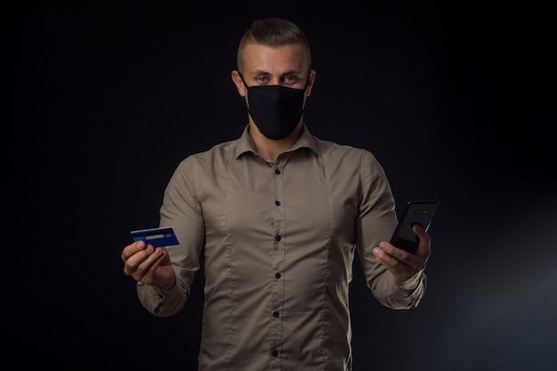 Zamówienia online w sezonie covid-19. mężczyzna na czarnej ścianie