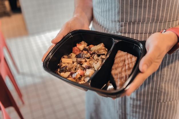 Zamówienie dla klienta. kelner ubrany w czerwoną rękę i zegarek w paski w fartuchu trzyma pudełko z zamówieniem dla klienta