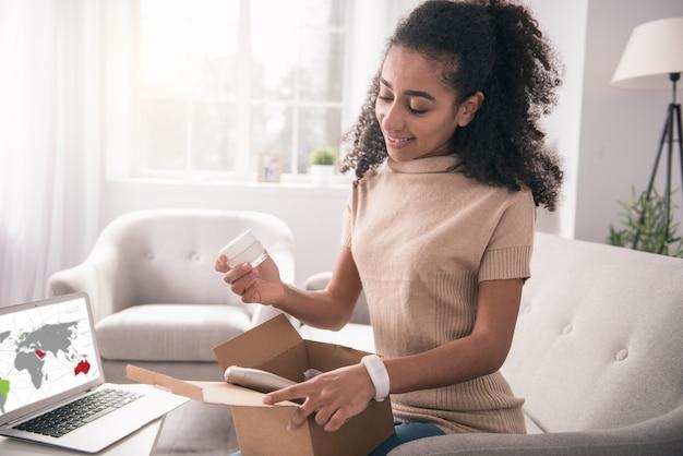 Zamówienie internetowe. radosna pozytywna kobieta otwierająca pudełko, patrząc na swoje zamówienie
