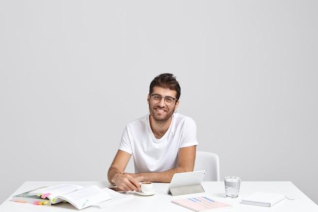 Zamożnie uśmiechnięty męski przedsiębiorca w białej koszulce