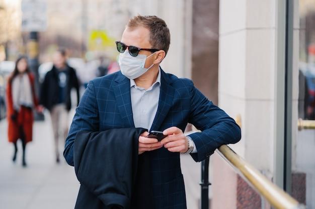 Zamożny biznesmen w strojach formalnych pozuje na ulicy, nosi maskę medyczną podczas wybuchu koronawirusa