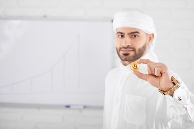 Zamożny przystojny muzułmański mężczyzna w tradycyjnej islamskiej odzieży trzyma złotego bitcoin przed białą deską