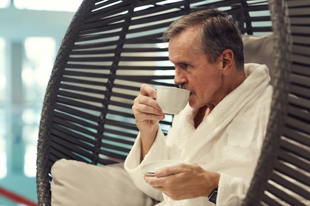 Zamożny starszy mężczyzna cieszy się kawą w zdroju kurorcie