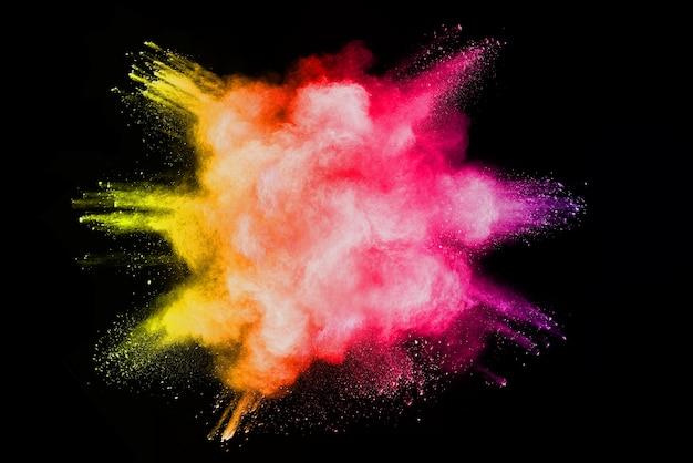 Zamrożenie ruchu kolorowe eksplozje proszku na białym tle na czarnym tle