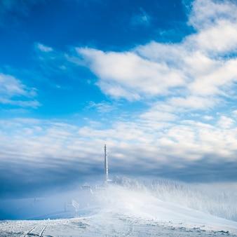 Zamrożona wieża komórkowa. zamarznięta telekomunikacja góruje z naczyniem i mobilną anteną przeciw niebieskiemu niebu w zim górach.