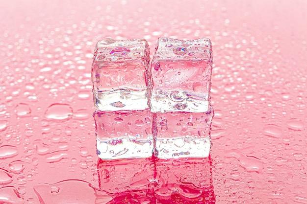 Zamrożone kostki lodu na mokrym różowym tle