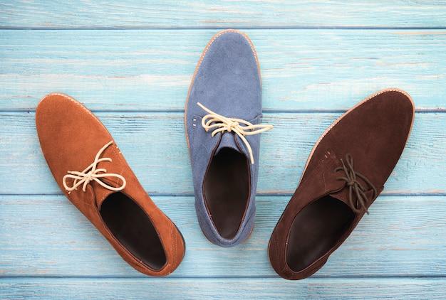 Zamszowy mężczyzna kostki but na białym tle na drewniane tła. zdjęcia mody obuwia reklamowego.