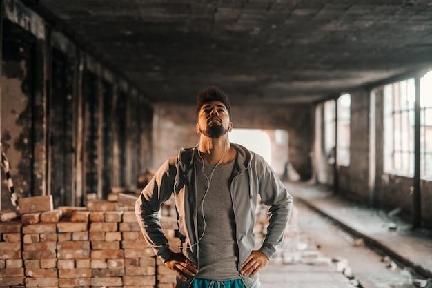 Zamyka up amerykanina afrykańskiego pochodzenia mężczyzna przyglądający up i trzyma ręki na biodrach podczas gdy stojący w starej ceglanej fabryce. koncepcja miejskiego stylu życia.