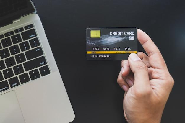 Zamyka up azjatyccy mężczyzna trzyma kredytową kartę i robi zakupy online przez laptopu