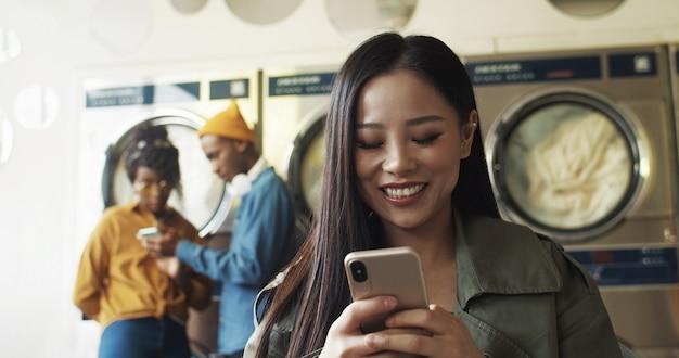Zamyka up azjatycka dosyć rozochocona kobieta stuka wiadomość i sms na smartphone w pralnianym pokoju usługowym. piękna szczęśliwa dziewczyna pisać na maszynie na telefonie i czeka ubrania odziewa czyścić w pralni.