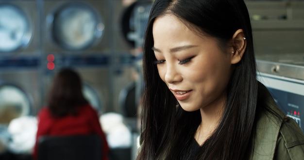 Zamyka up azjatycka ładna kobieta z długim ciemnego włosy stukaniem i texting wiadomość na smarphone podczas gdy stojący w pralnianym pokoju usługowym. piękna kobieta, wpisując na telefon i czekając na pranie.