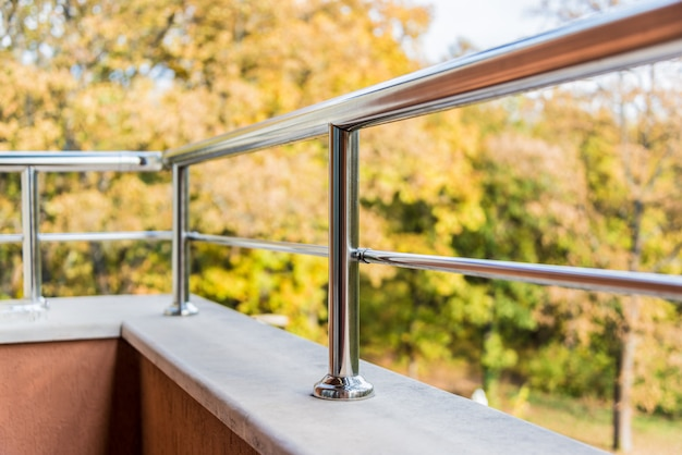 Zamyka up balkonowa metal balustrada. widok jesieni w