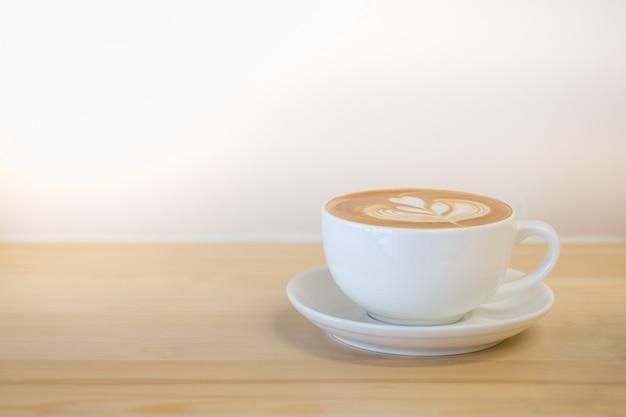 Zamyka up biała filiżanka gorący kawowy latte z mleko piany kształta kierową sztuką na drewnianym stole