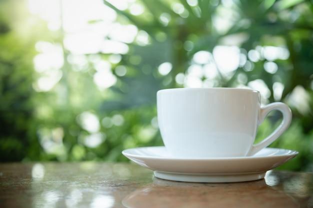 Zamyka up biała filiżanka i talerz gorąca kawa na drewnianym stole i zieleń liścia natury tle.