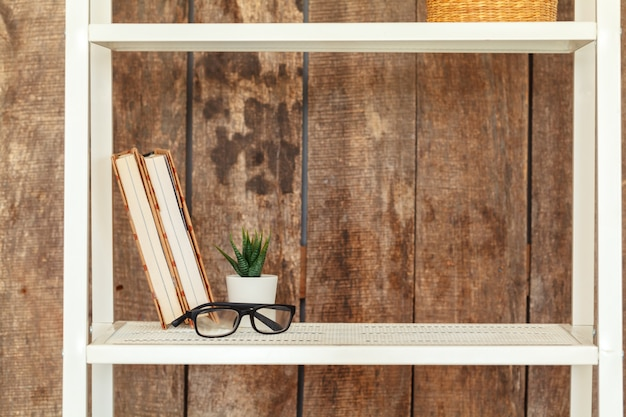 Zamyka up biały półka na książki przeciw grunge drewnianej ścianie