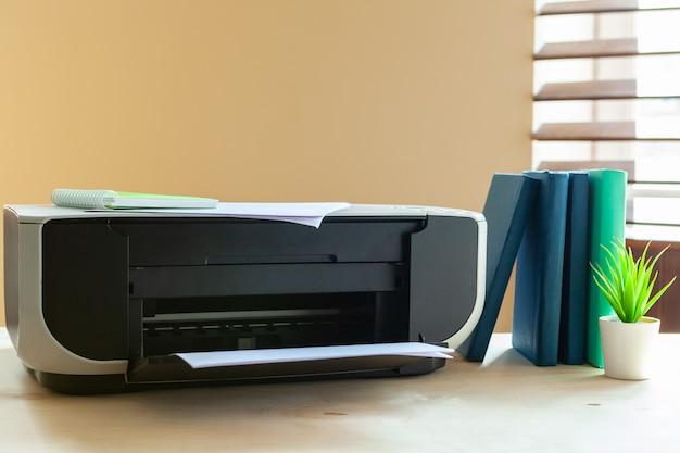 Zamyka up biurowy stół z drukarką na nim