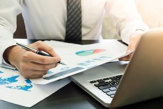 Zamyka up biznesmen analizuje inwestycj mapy i używa laptop na biurku.