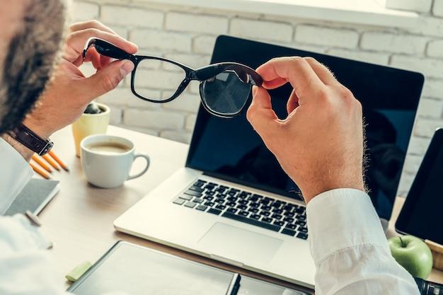 Zamyka up biznesmen przy jego pracującym stołem w biurze