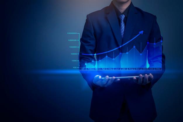 Zamyka up biznesmen trzyma pieniężnego wykres z pastylka komputerem