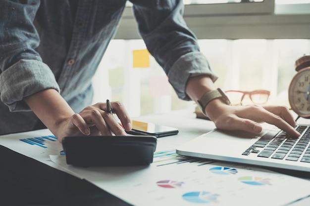 Zamyka up biznesmena lub księgowego ręki mienia pióro pracuje na kalkulatorze obliczać biznesowych dane