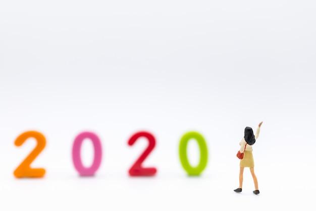 Zamyka up bizneswoman miniatury postaci fala z torebką na białym tle z 2020 plastikowymi kolorowymi liczbami.