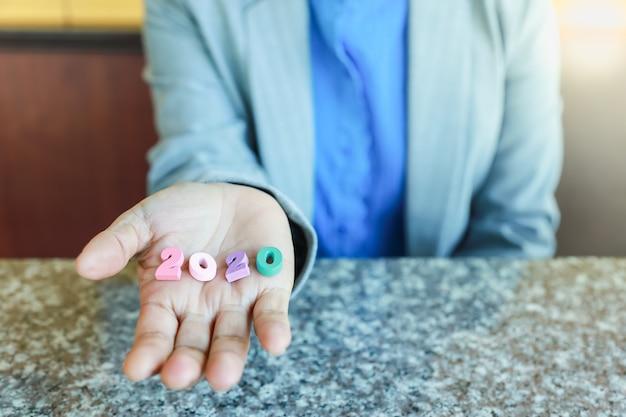 Zamyka up bizneswoman trzyma kolorową drewnianą liczbę 2020 w jej ręce.