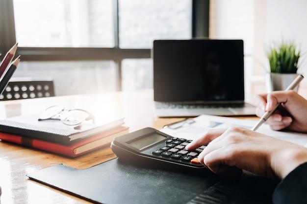 Zamyka up bizneswomanu lub księgowego ręki mienia pióro pracuje na kalkulatorze obliczać biznesowych dane