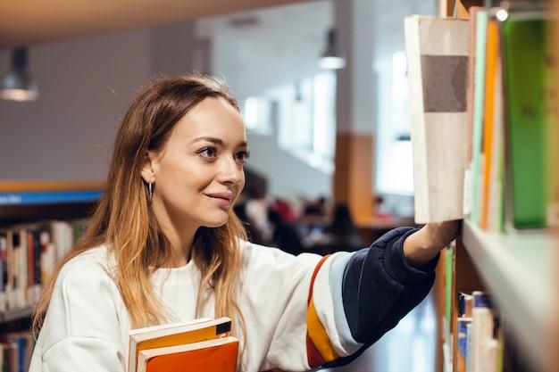 Zamyka up blondynki dziewczyna w bibliotece