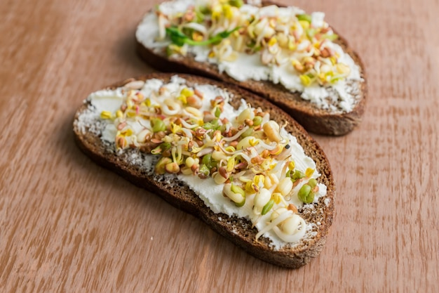 Zamyka up chleb żytni kanapki z kremowym serem i kiełkować mung fasolę, orzech włoski, słonecznik i len na drewnianej ścianie. wegańska, surowa dieta.