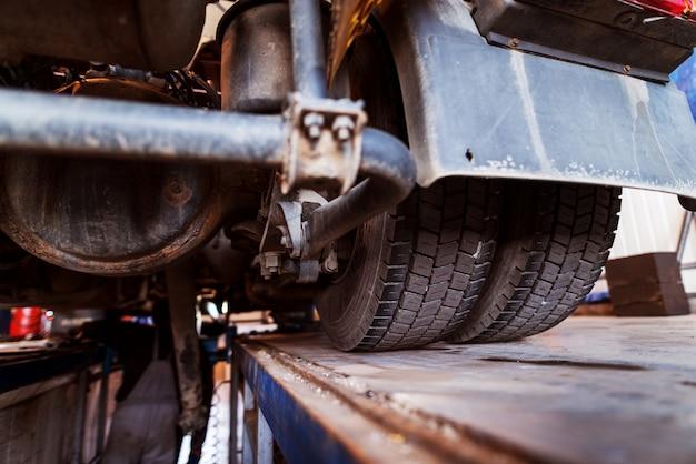 Zamyka up ciężarowe opony. naprawiać starą ciężarówkę w samochodowym warsztacie.
