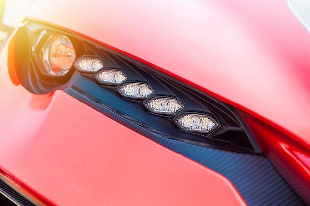 Zamyka up czerwony sportowy luksusowy samochód w zmierzchu