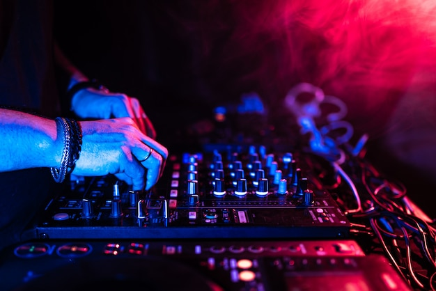 Zamyka up dj ręki kontroluje muzycznego stół w noc klubie.
