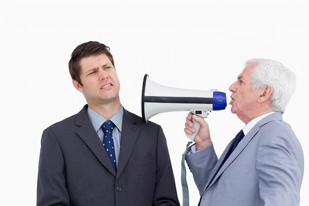 Zamyka up dojrzały biznesmen wrzeszczy przy kolegą z megafonem