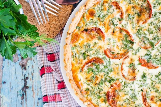 Zamyka up domowej roboty francuski quiche kulebiak z pomidorem, serem i ziele na talerzu na drewnianym stole. widok z góry