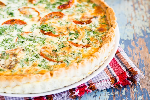 Zamyka up domowej roboty francuski quiche kulebiak z pomidorem, serem i ziele na talerzu