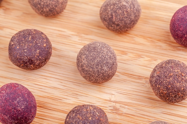 Zamyka up domowej roboty surowe weganin kakaowe energetyczne piłki na drewnianej desce na stole
