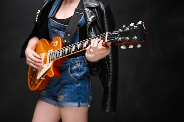 Zamyka up dziewczyn ręki na gitarze nad czarnym tłem.