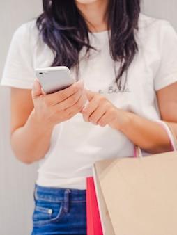 Zamyka up dziewczyna patrzeje jej smartphone mienia torba na zakupy w centrum handlowym.
