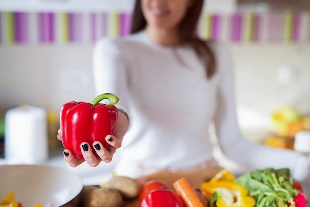 Zamyka up dziewczyny mienia czerwona papryka w ona ręki. nacisk kładziony jest na paprykę.