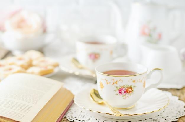 Zamyka up filiżanka herbata na stole z rocznika brzmieniem