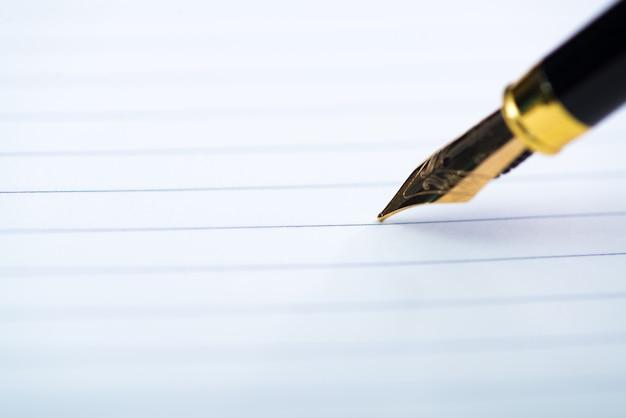 Zamyka up fontanny pióro lub atramentu pióro z notatnika papierem
