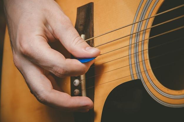 Zamyka up gitarzysta ręka bawić się gitarę