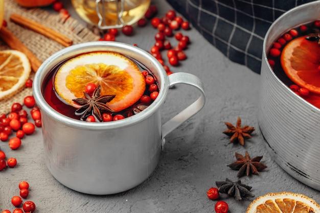 Zamyka up grzana wino filiżanka z pikantność i jagodami na popielatym stole