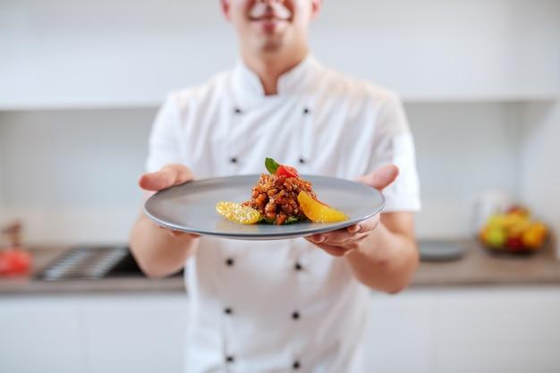 Zamyka up kaukaski szef kuchni w jednolitym mienie talerzu z łososiem i pomarańczową owoc.