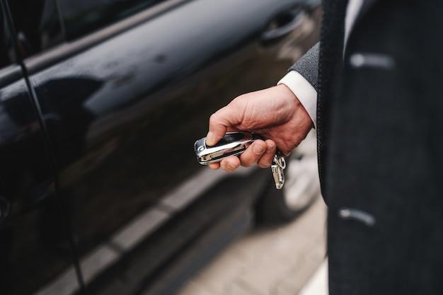 Zamyka up kaukaski w średnim wieku mężczyzna blokuje jego samochód w kostiumu.
