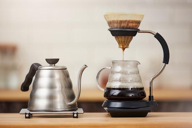 Zamyka up kawowi parzenie gadżety na drewnianym baru kontuarze.