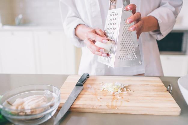 Zamyka up kobiet ręki trzyma tarkę i jajko. ona kroi to na kawałki. na stole jest deska, miska i nóż.