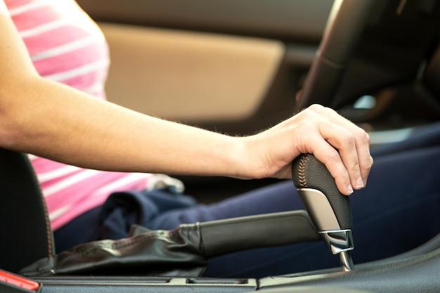 Zamyka Up Kobieta Kierowca Trzyma Jej Rękę Na Automatycznej Zmiany Biegów Kija Jeżdżeniu Jako Samochód. Premium Zdjęcia